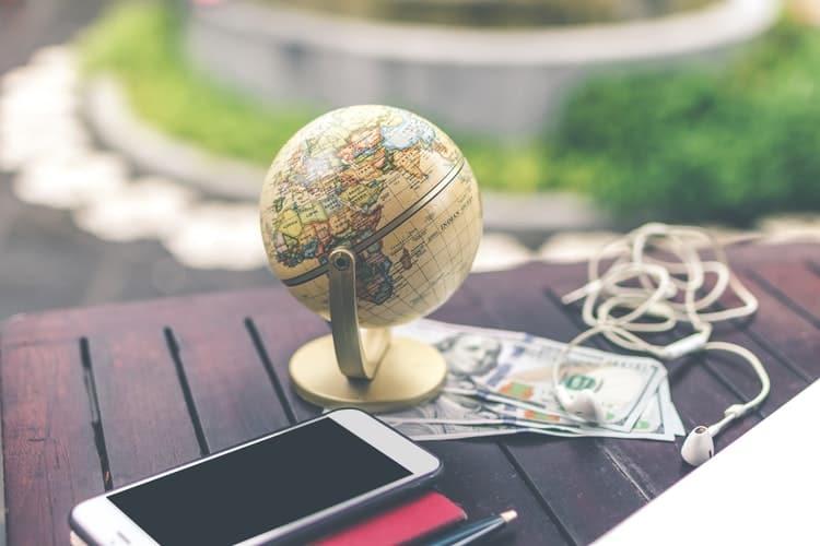 Mappamondo con telefono e soldi